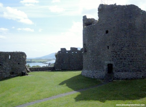 The keep, curtain wall with visible crenellations, Mourne Mountains, and Newcastle Harbour.